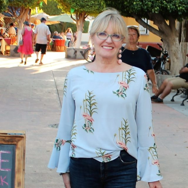 Jennifer Connolly of A Well Styled Life wearing a tropical print blouse from Ann Taylor
